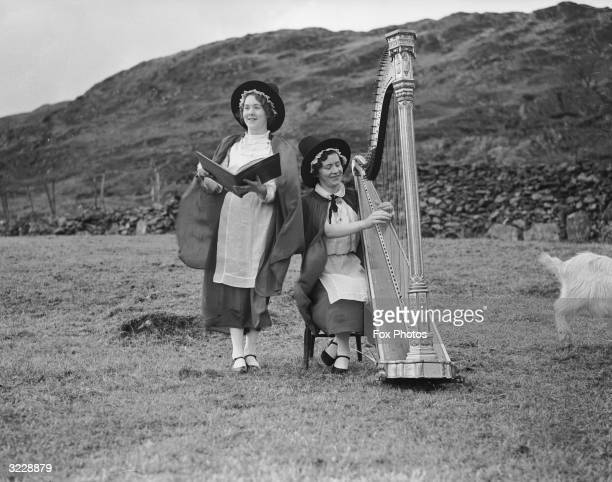Two members of the Eryri Harp Choir rehearsing in a field at Hafod Y Porth near Bedgelert
