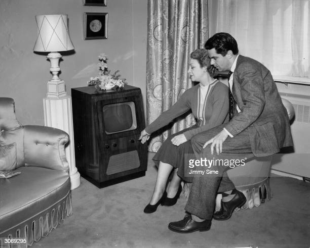 A couple watching television in one of the 219 rooms of the new Westbury Hotel built on a bombsite on the corner of Bond Street and Conduit Street...