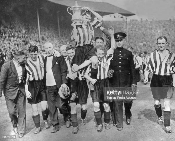 The players of Sunderland Football Club carry their captain Raich Carter and the FA Cup shoulder high in celebration of their 31 victory over Preston...