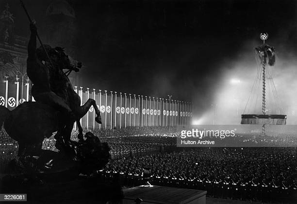 View of a Nazi demonstration outdoors at night in the Lustgarten with an equestrian statue in the foreground Berlin Germany General Field Marshal...