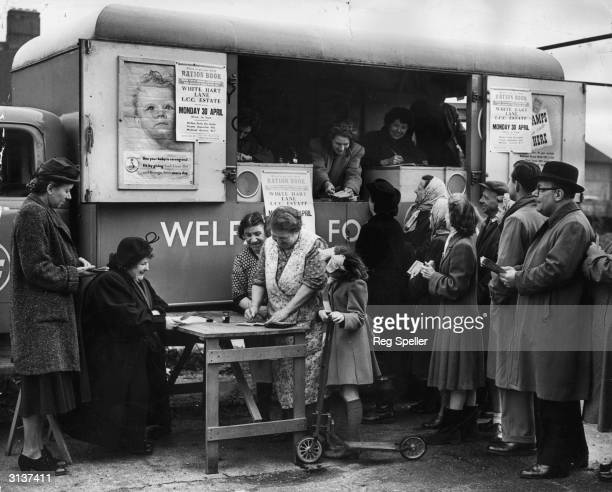 Miss I Maguire of the Tottenham Food Office distributes ration books to local housewives from a new mobile office parked on White Hart Lane London