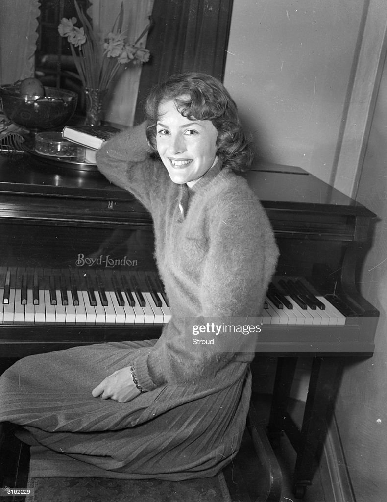 English actress and singer <a gi-track='captionPersonalityLinkClicked' href=/galleries/search?phrase=Petula+Clark&family=editorial&specificpeople=208081 ng-click='$event.stopPropagation()'>Petula Clark</a> seated at a piano.