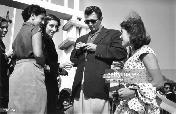 US actor Robert Mitchum signing autographs for fans at the Cannes Film Festival French actress Lise Bourdin is on the right Original Publication...