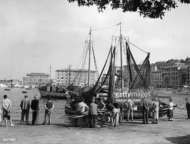 A fishing boat is about to be unloaded in the harbour at San Margherita Genoa Italy