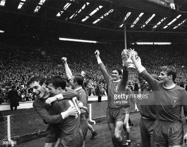 Captain of Liverpool FC Ron Yeats holds the FA cup aloft and raises his arms in triumph as his victorious team do a lap of honour