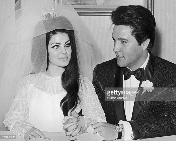 American rock n' roll singer and actor Elvis Presley sits and holds hands with his bride Priscilla Presley on their wedding day Las Vegas Nevada She...