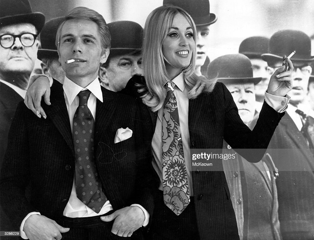 Pop singer and actor Adam Faith (1940 - 2003) and his wife, model Jackie Irving, wearing 'his and her' suits and ties in front of a backdrop of city gents.