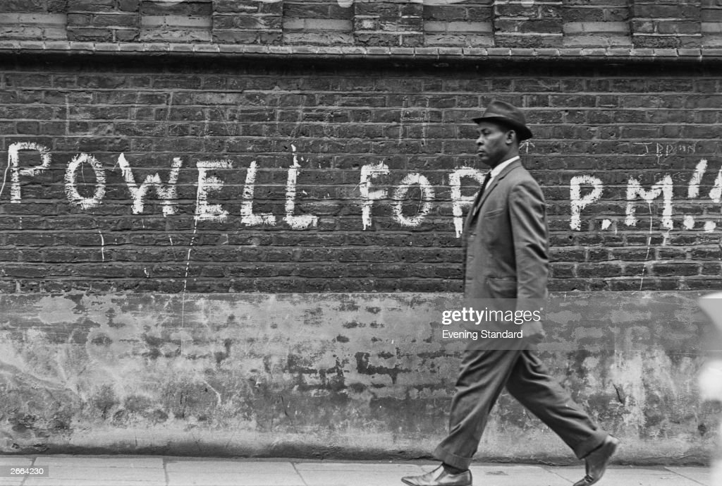 A black man walking past graffiti stating 'Powell For PM' (prime minister), referring to British Conservative politician Enoch Powell who caused controversy with his outspoken attitude to black immigration and racial integration culminating in his infamous 'Rivers of Blood' speech.