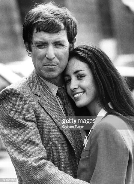 British actor John Nettles as television detective 'Bergerac' embraces costar Cecile Paoli on location in Jersey