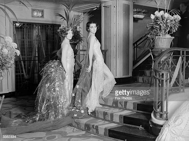 Two women wearing diaphanous ballgowns with long trains before they go to a 'Galaxy Ball'