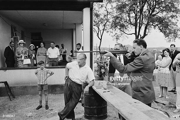 Rhodesian Prime Minister Ian Smith tries his hand at a rifle range during an outdoor fete in Gwanda Rhodesia
