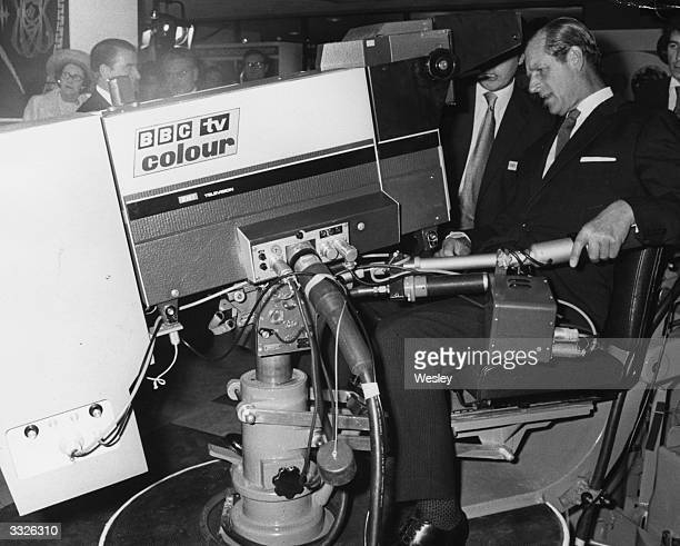 Prince Philip the Duke of Edinburgh tries his hand as a television cameraman at a technical exhibition arranged in conjunction with the 50th...