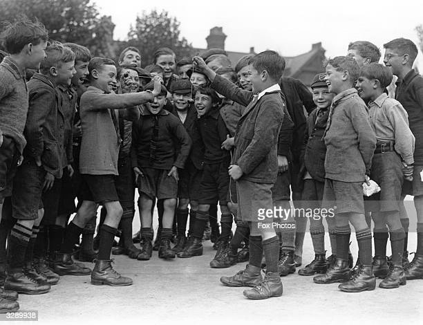 Boys in their uniform shorts and long socks conker fighting in the conker season in Hornsey London 1926
