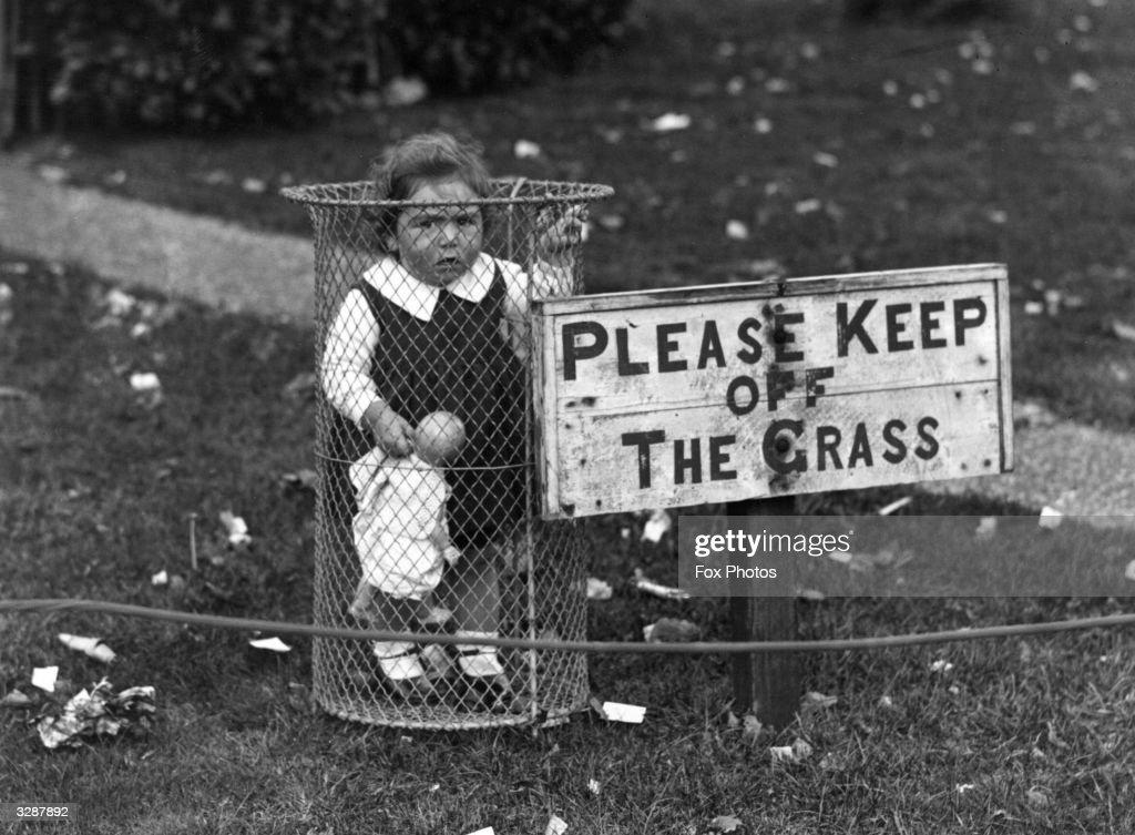 A child standing in a park rubbish bin.