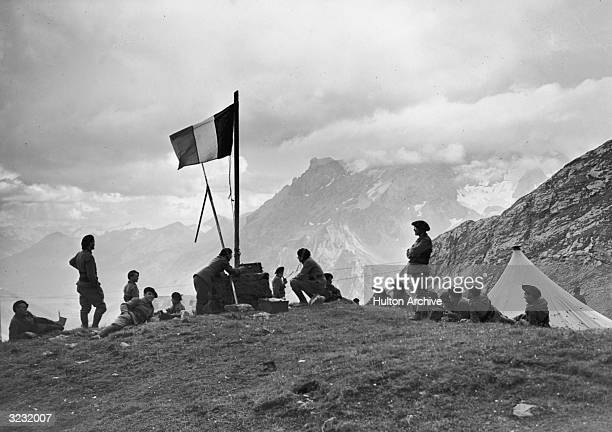 A French army radio squad waving a French flag waits at a camp atop a misty peak in the French Alps just after the Nazi invasion of Poland France...