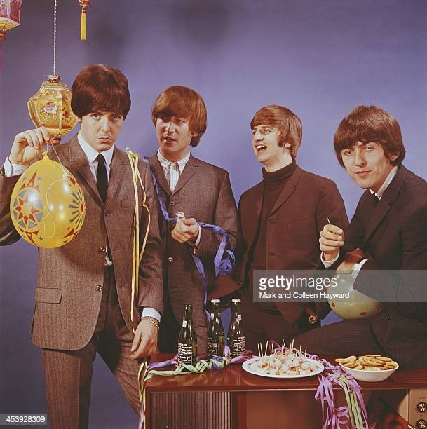 The Beatles posed with bottles of beer and party snacks and balloons in October 1964 Left to right Paul McCartney John Lennon Ringo Starr and George...