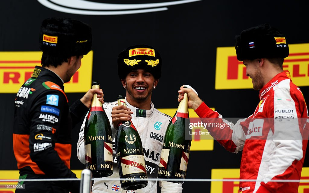 1st placed Lewis Hamilton of Great Britain and Mercedes GP (c) celebrates with 3rd placed Sergio Perez of Mexico and Force India and 2nd placed Sebastian Vettel of Germany and Ferrari after the Formula One Grand Prix of Russia at Sochi Autodrom on October 11, 2015 in Sochi, Russia.