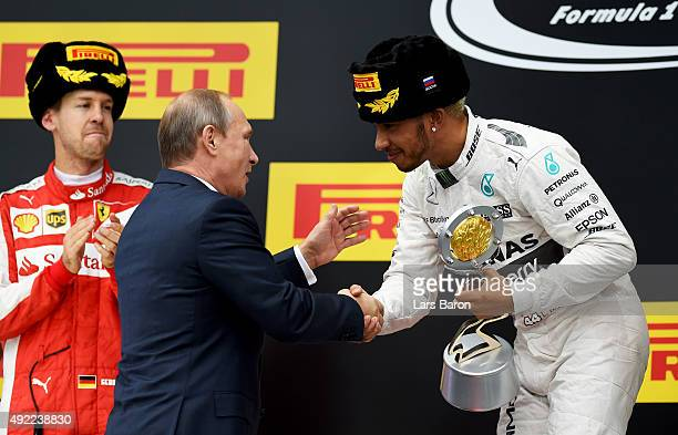 1st placed Lewis Hamilton of Great Britain and Mercedes GP shakes hands with Russian president Vladimir Putin after winning the Formula One Grand...