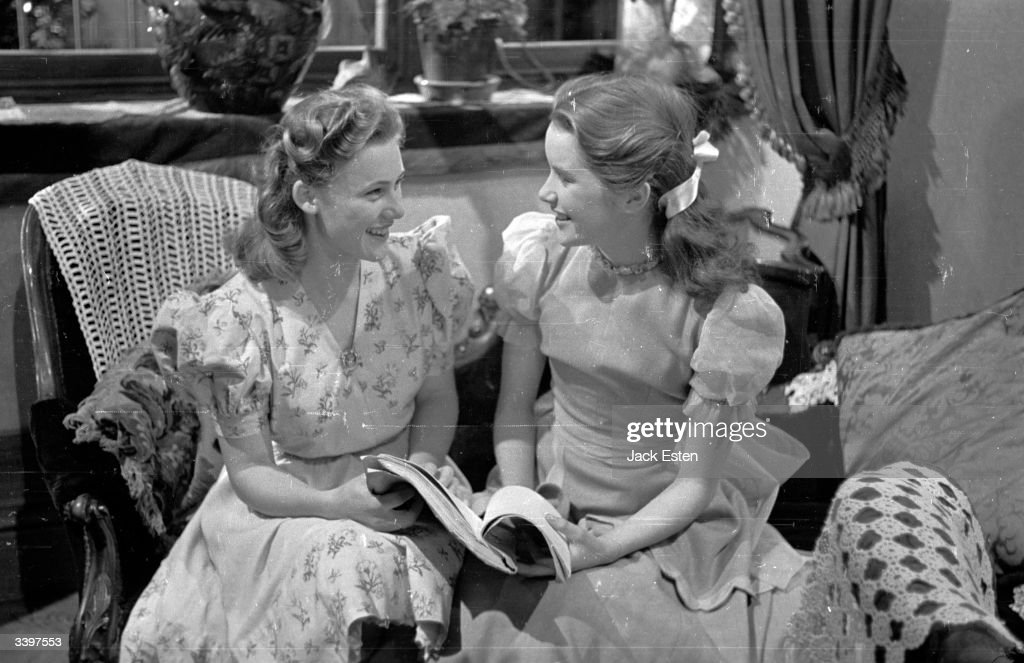 British child actress Sally Ann Howes chats with her stand-in Kay Matthews on the set of her fourth film, 'Pink String and Sealing Wax', at Ealing Studios, London. Original Publication: Picture Post - 2020 - Her Fourth Film At Fourteen - pub. 1945