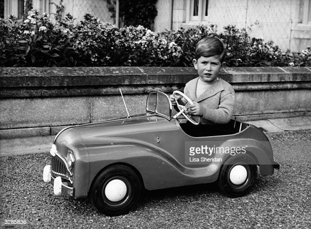 Prince Charles aged 4 driving a toy car in the grounds of Balmoral Castle in Aberdeenshire Scotland Queen Victoria's husband Prince Albert purchased...