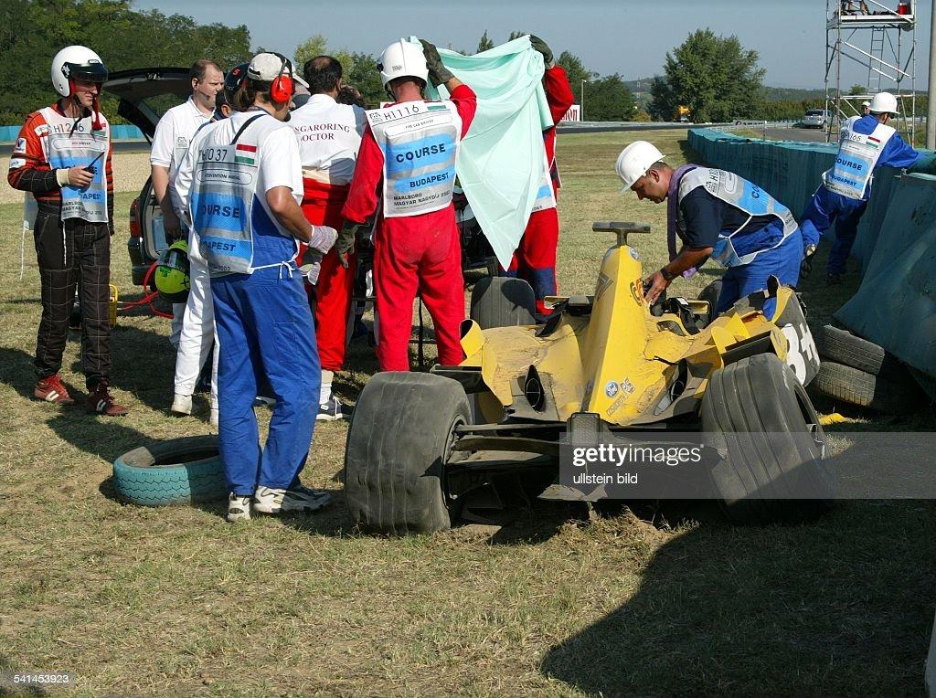 Sportler, Motorsport, Formel-1, GrossbritannienJordan Fordwird nach seinem Unfall beim Grossen Preis von Ungarn medizinisch versorgt. Rechts sein zerstörter Ford.