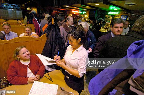 DENVER COLORADO NOVEMBER 30 2006Server Nikki Rivera <cq> takes down an order at a booth as customers waiting to be seated line the aisle between the...