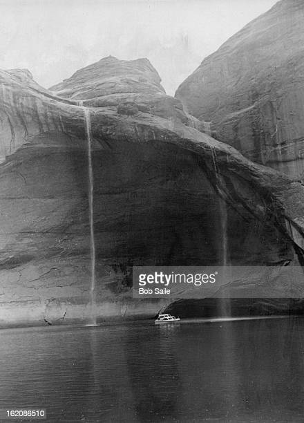 OCT 1972 OCT 8 1972 20Foot Boat On Lake Powell Is Dwarfed By Waterfalls Rare desert rainstorm flooded flattop cliffs above the lake sent runoff...