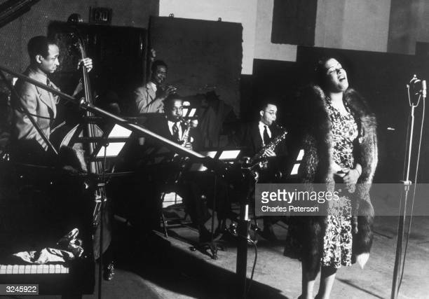 American jazz singer Billie Holiday performs with left to right bassist Johnny Williams trumpeter Frankie Newton and saxophonists Stan Payne and...