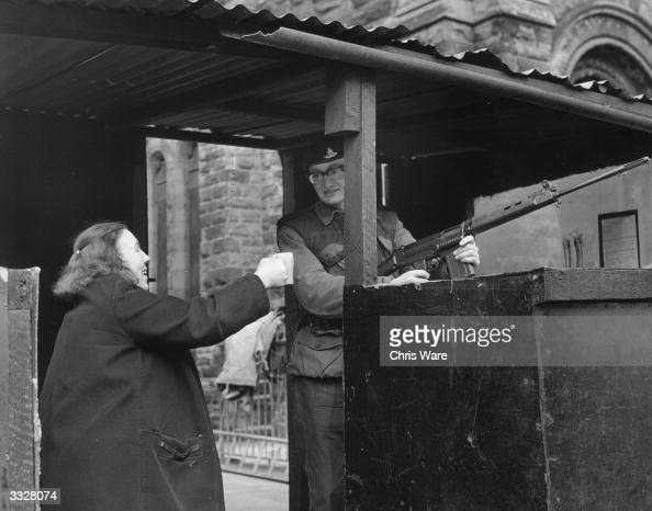 A woman offers a cup of tea to a soldier manning a check point in a Belfast street
