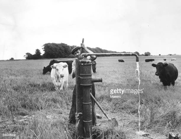 A famer operating a hand pump to draw water from a well on Colonel Backford's farm at Compton Abdale in Gloucester