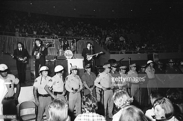 A line of police officers prevent fans from getting too close as The Beatles perform behind them on stage at the Convention Hall Las Vegas