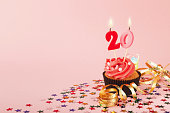 20th birthday cupcake with candles, sprinkles and ribbon on pink background. Card mockup, copy space. Birthday, party, holiday concept