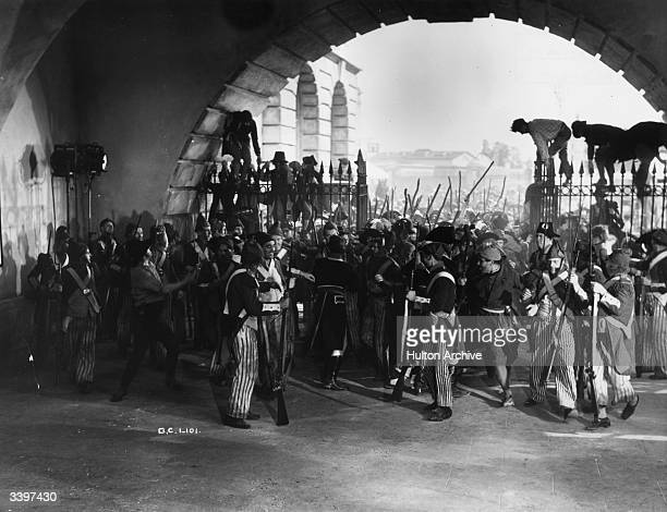 An angry mob being filmed storming a gateway guarded by soldiers for a scene in 'The Return of the Scarlet Pimpernel' directed by Hans Schwartz for...