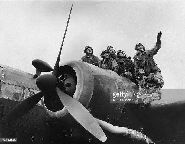 A group of Polish pilots balance on the wing of a Wellington bomber to watch aircraft take off from a British RAF base These men and others like them...