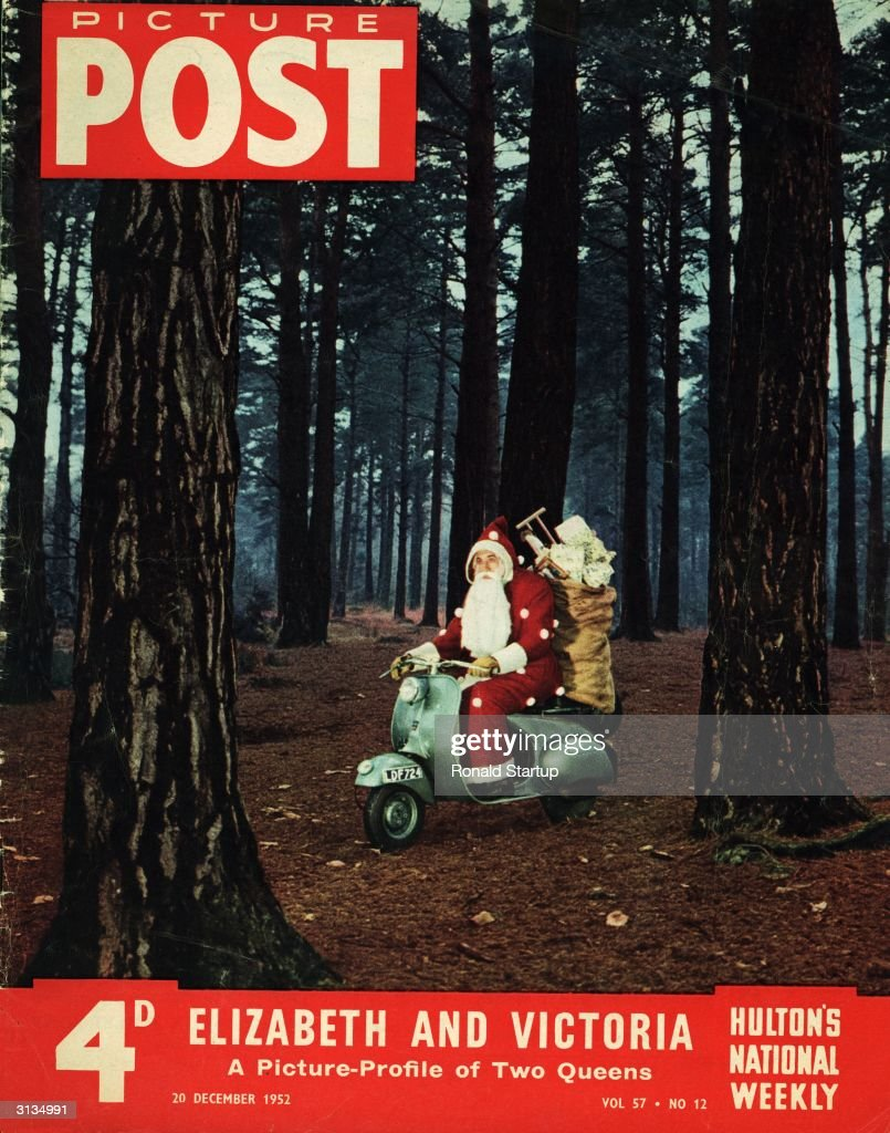 Father Christmas with a sackful of toys is riding a motor scooter through a pine wood. Original Publication: Picture Post - Cover - pub. 1952
