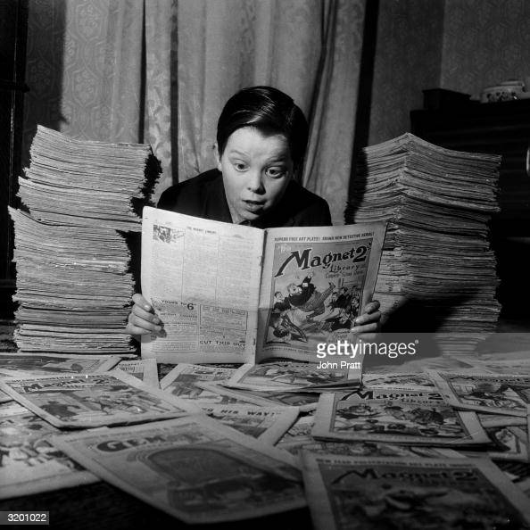 Thirteen yearold Michael Harris avidly reads one of the thousands of vintage comics in the collection of his neighbour Leonard Packham of Dulwich...