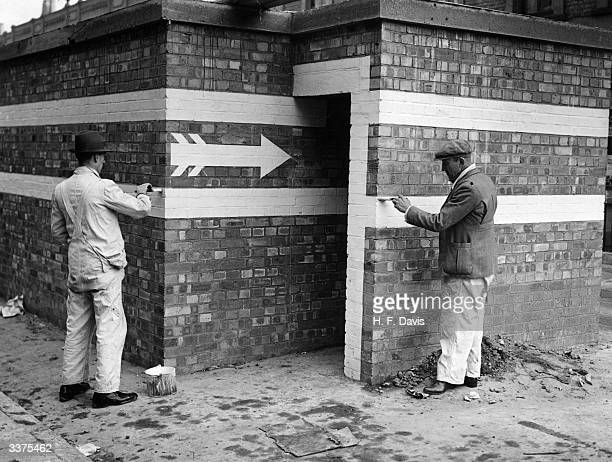 Workmen painting directional arrows by the entrance to a public air raid shelter in Parkstone Road Peckham London during World War II