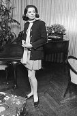 Fulllength portrait of American broadcast journalist Barbara Walters wearing a miniskirt leaning against a piano in her home at 171 West 57th Street...
