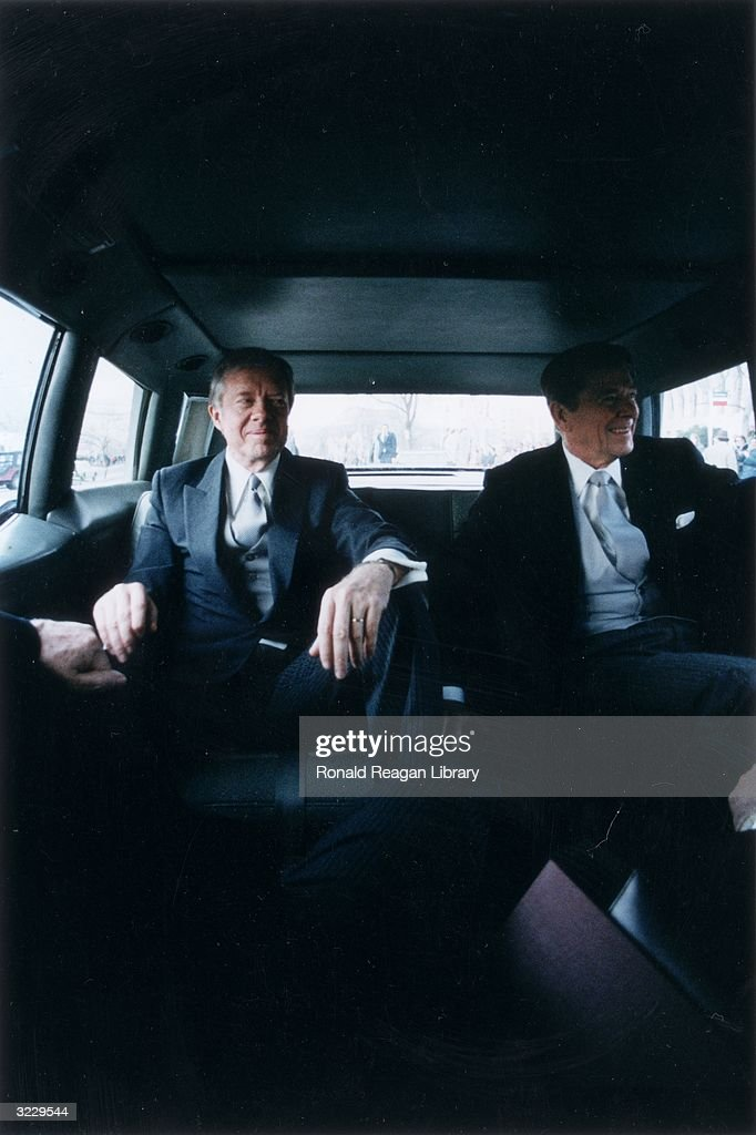Outgoing US President Jimmy Carter sits with presidentelect Ronald Reagan in the back of a limousine en route to Reagan's Presidential Inauguration...