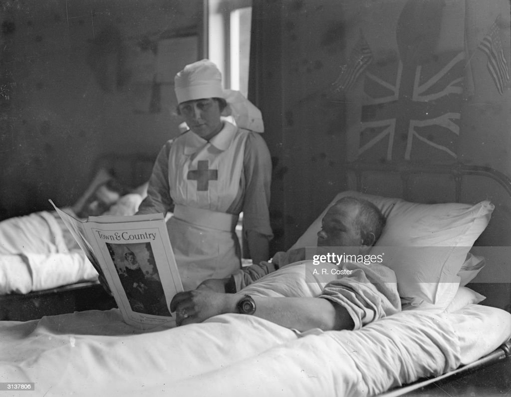A wounded American in a London hospital reads a magazine with a red cross nurse by his bedside.