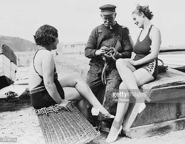 An old 'salt' showing two girls in swimwear how to tie a few rope knots at Tenby South Wales