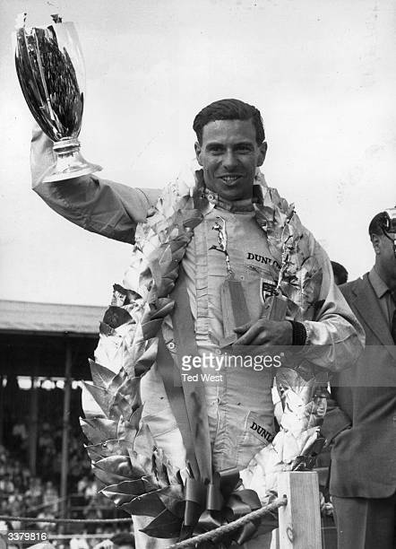 British motorracing driver Jim Clark with his trophies and garland after winning the British Grand Prix at Silverstone with an average speed of 10735...