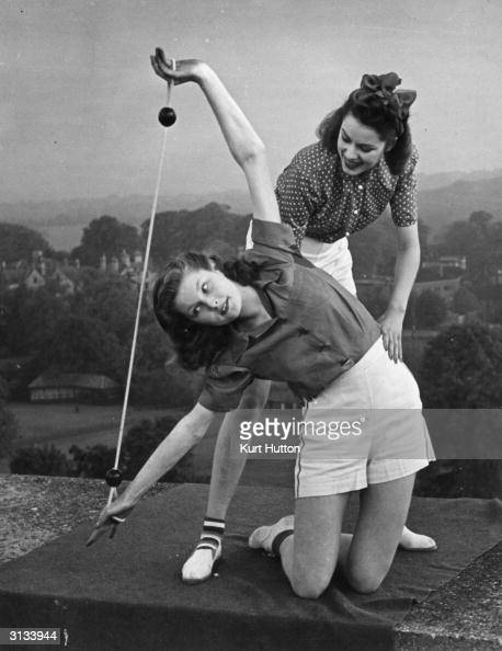 Pamela Minchin and April Stride demonstrate the new 'litheline' exercises promoted by Helena Rubinstein on the roof of a block of flats in London...