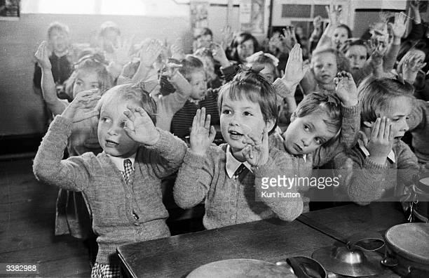 The Good quadruplets fiveyearold Jennifer Bridget Elizabeth and Frances singing 'Ten Men Went To Mow' at school in the village of Westerleigh near...