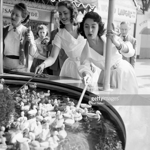Two young women hooking floating ducks at a fun fair in Battersea Park London The models are Valerie Carton and Patricia Webb Original Publication...