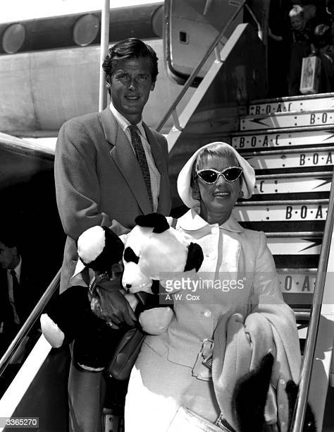 Welsh singer Dorothy Squires arriving on vacation at London Airport with her husband Roger Moore and a large stuffed panda