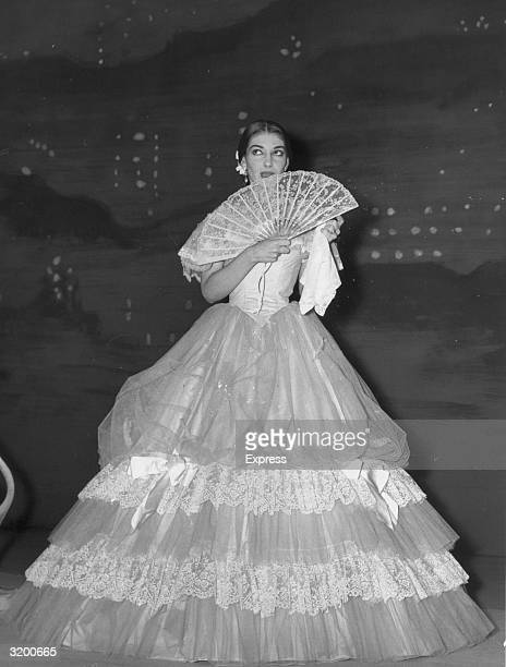 GreekAmerican opera singer Maria Callas in costume holds a fan while waiting in the wings before a performance of 'La Traviata' at the Royal Opera...