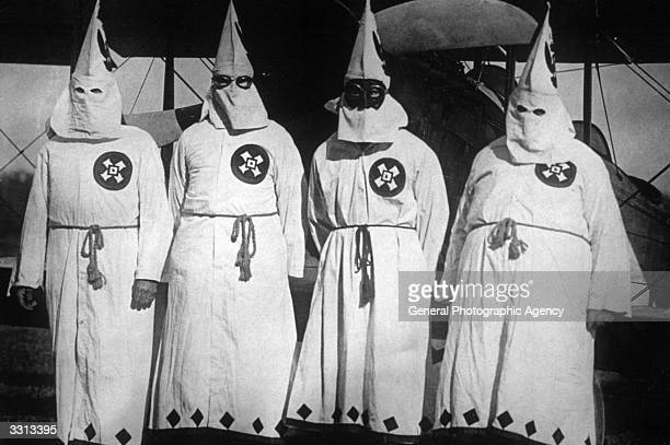 Members of the white supremacist movement the Ku Klux Klan standing by an aeroplane out of which they dropped publicity leaflets over Washington DC