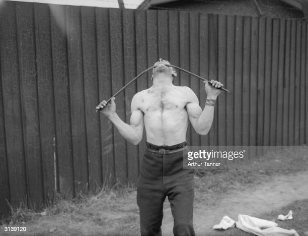 Strong man George Challard of Woowich London who can bear the weight of a car on his neck shows he can bend an iron bar with his teeth