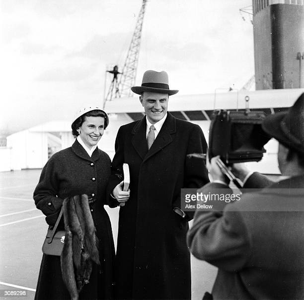 Evangelist Billy Graham with his wife being interviewed on the deck of SS United States as he arrived in England where he will preach in Harringay...